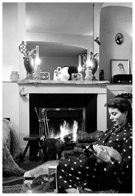 Bettina taking a well-deserved rest in her Paris apartment with her two Siamese cats, photo by Nat Farbman, Feb. 1952