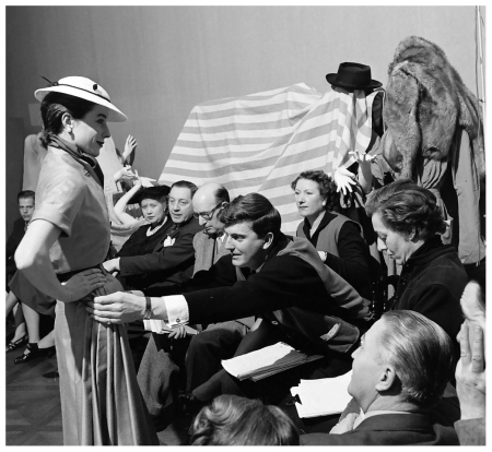 Hubert de Givenchy adjusts the skirt of one of his designs on Bettina for his first Spring collection, photo by Nat Farbman, Feb. 1952