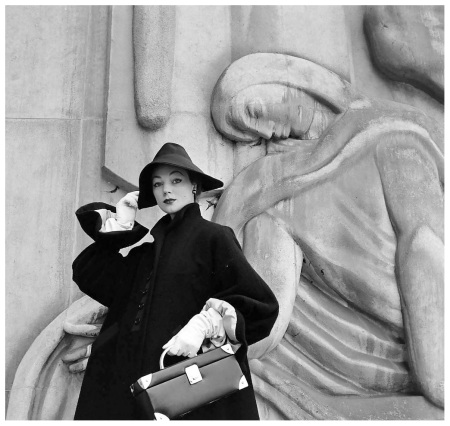 Ivy is wearing Givenchy's big-sleeved coat of navy wool with new wrist-ruffle cuffs and Garbo-slouch hat, photo by Nat Farbman, Paris, Feb. 1952