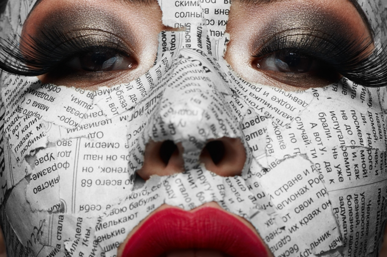 Beautiful girl with big Eyelashes, pink Lips and Newspaper on her Face