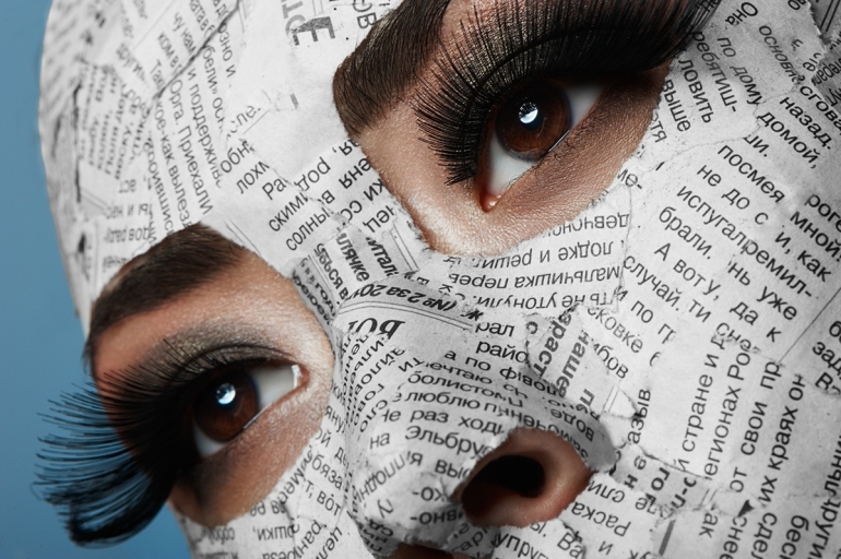Asian Girl with long Eyelashes and Newspaper on her Face