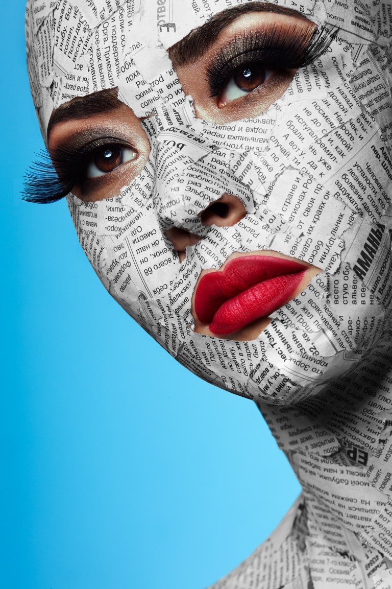 Beauty asian Girl with pink Lips and Newspaper on Face