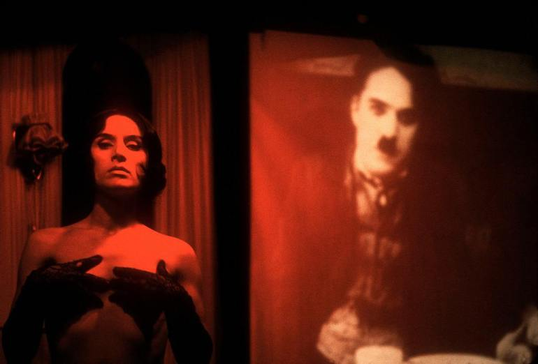 A-stripper-disrobes-in-front-of-a-silent-film-of-Charlie-Chaplin-at-the-Kino-club-Berlin-1958.