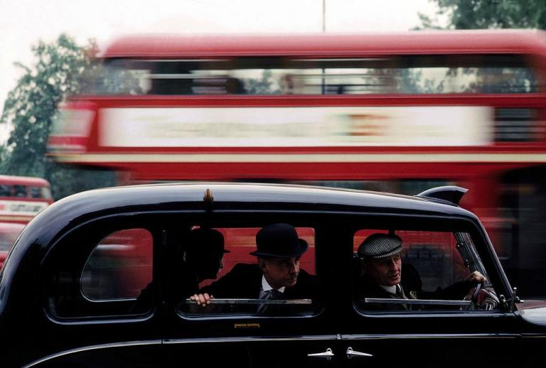 Taxi-riders-with-London-bus-in-the-background-London-1964.